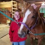 IVI client petting horse in stable