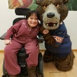 Woman in wheelchair posing with Bears mascot