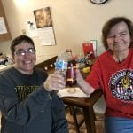 Two women clinking bottles and smiling