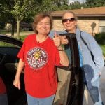 Senior woman with thumbs up entering car